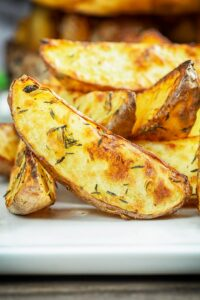 Portrait close up image of potato wedges served on a white plate