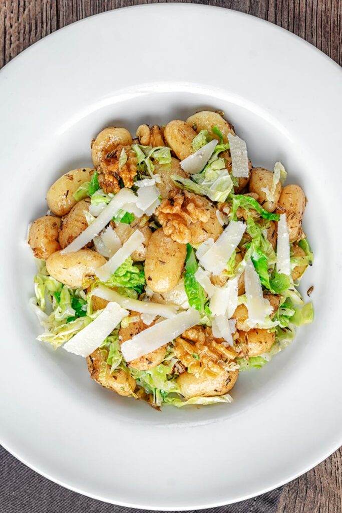 Portrait overhead image of a quick potato gnocchi meal featuring walnuts and cabbage served in a white bowl