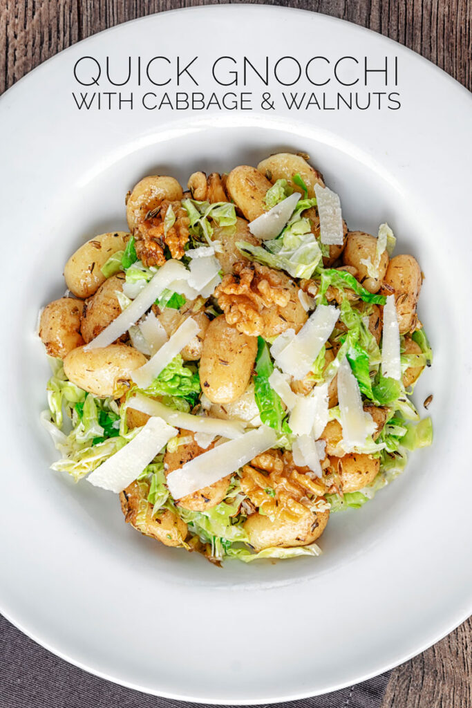 Portrait overhead image of a quick potato gnocchi meal featuring walnuts and cabbage served in a white bowl with text overlay