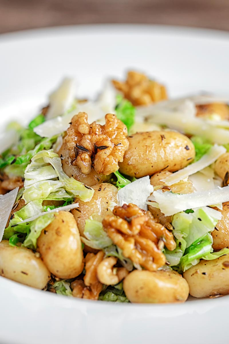 Portrait close up image of a quick potato gnocchi meal featuring walnuts and cabbage served in a white bowl