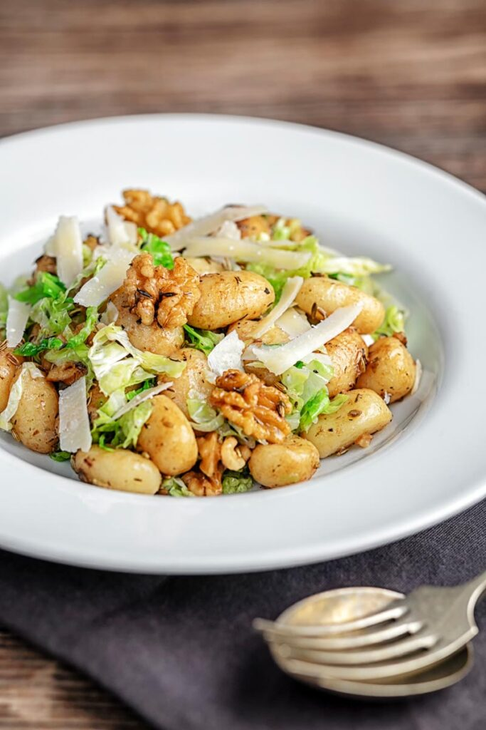 Portrait image of a quick potato gnocchi meal featuring walnuts and cabbage served in a white bowl