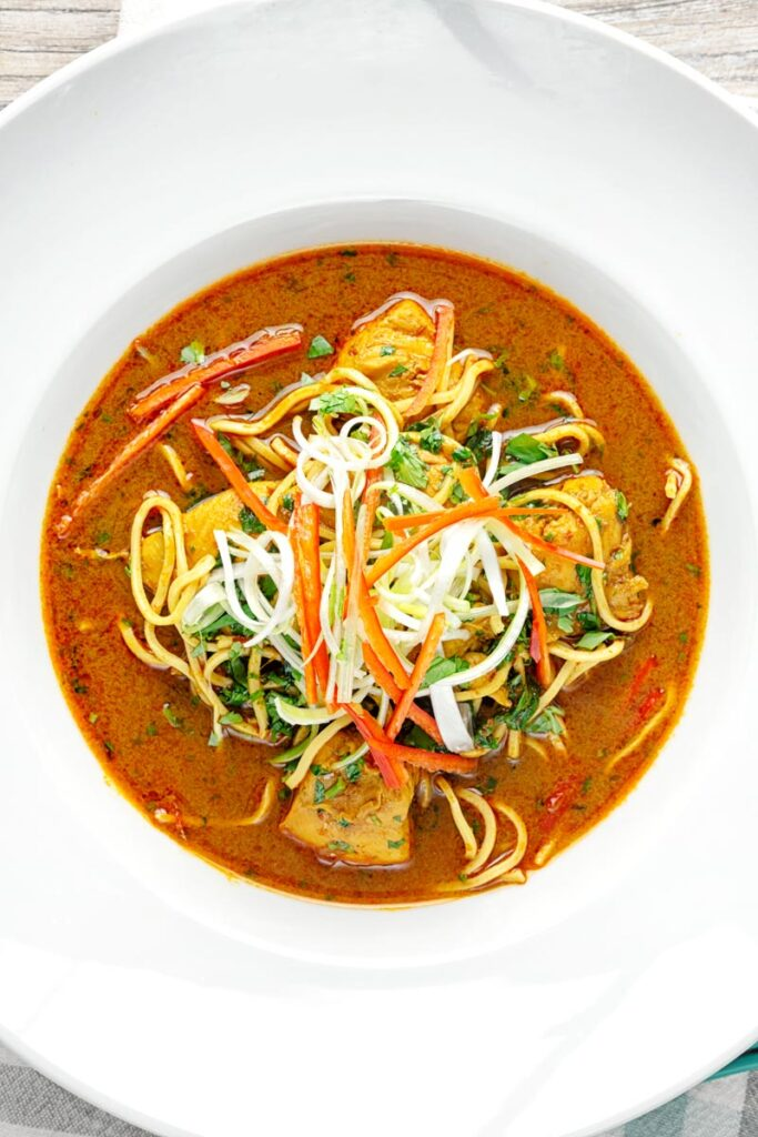 Portrait overhead image of a Thai inspired chicken noodle soup with a garnish of shredded spring onions and red chilli peppers