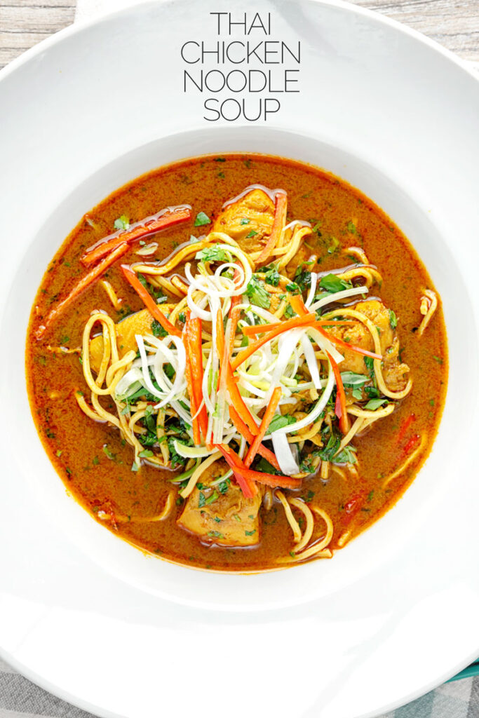 Portrait overhead image of a Thai inspired chicken noodle soup with a garnish of shredded spring onions and red chilli peppers with text overlay