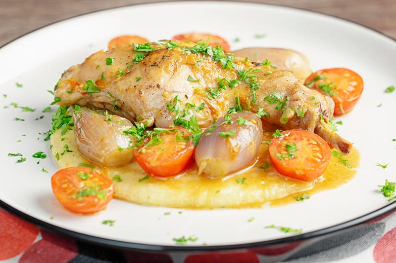 Landscape image of rabbit cacciatore featuring, rabbit legs shallots and cherry tomatoes served on cheesy polenta with lots of parsley