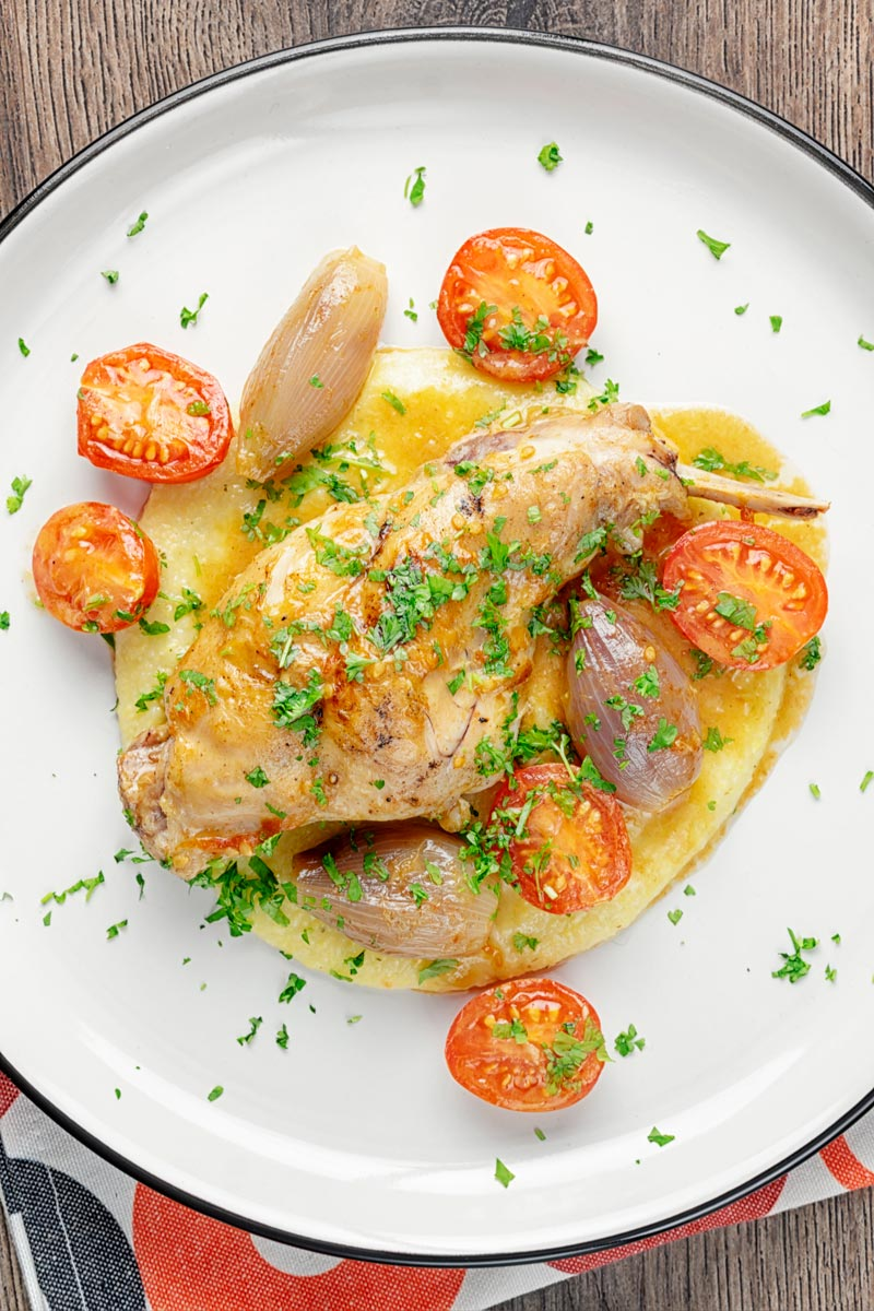 Square overhead image of rabbit cacciatore featuring, rabbit legs shallots and cherry tomatoes served on cheesy polenta with lots of parsley