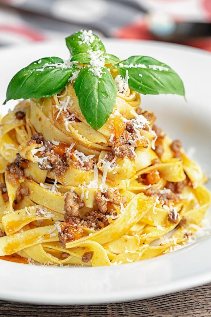 Portrait image of pasta served with a ragu bolognese meat sauce served in a white bowl with basil and grated Parmesan cheese