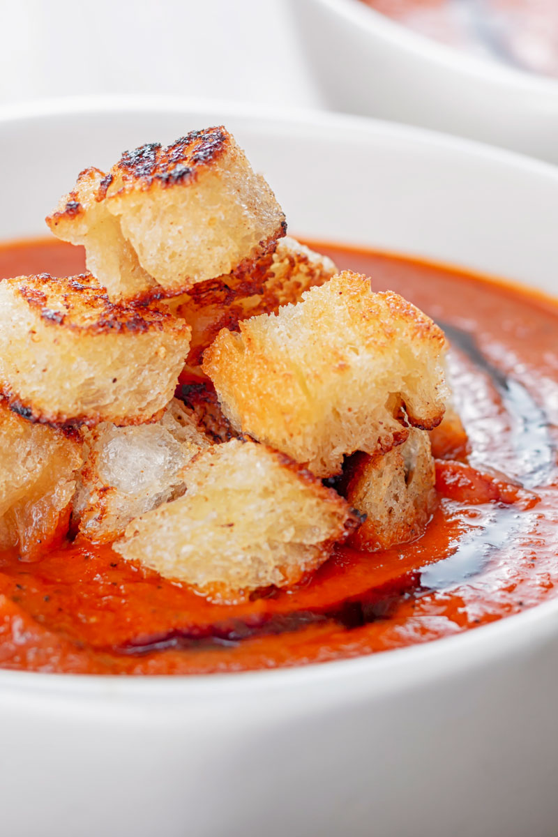 Portrait image of a tower of toasted croutons served with tomato soup