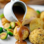Portrait image of gravy being poured over sage and onion stuffing balls with text overlay