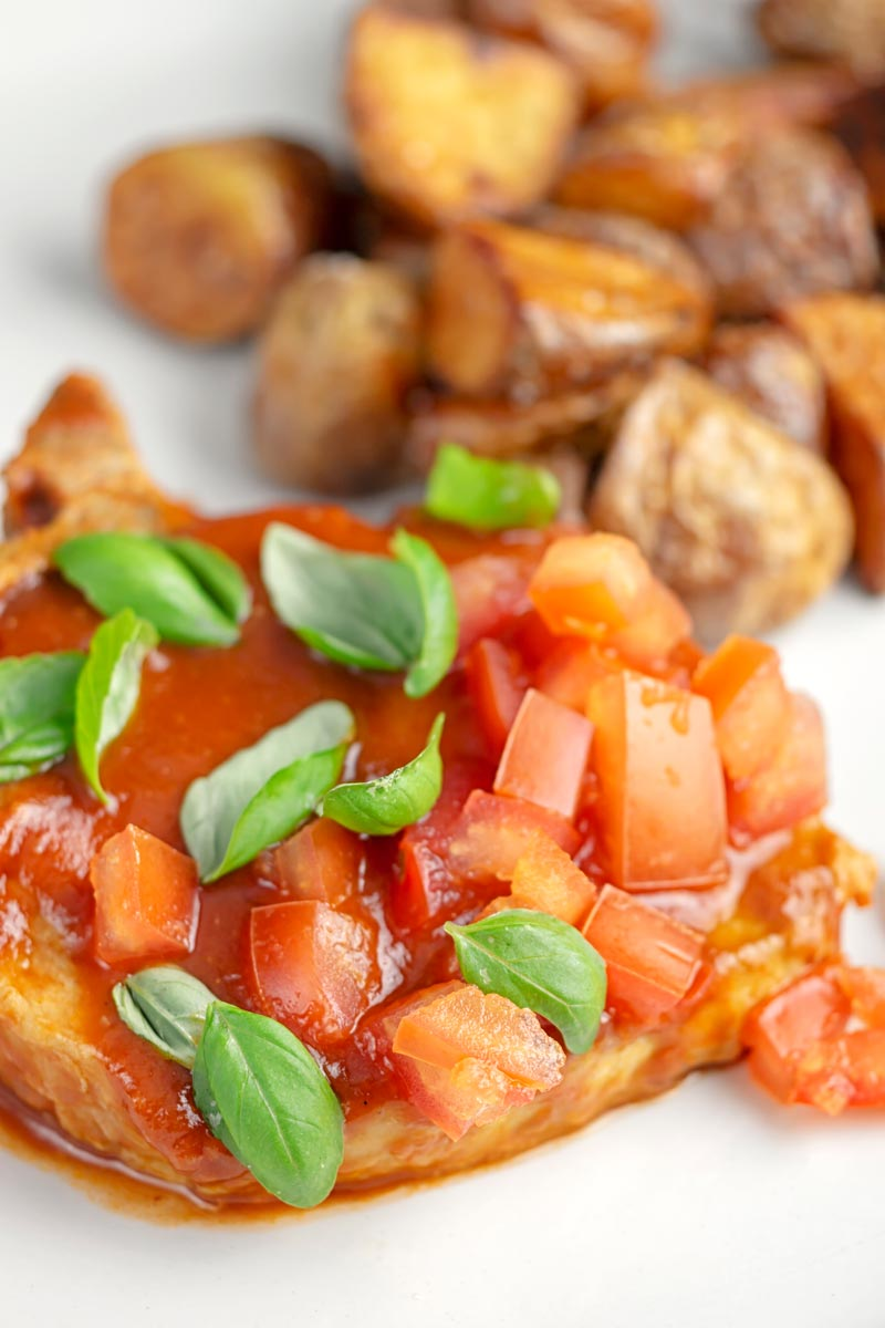 A portrait close up image of a slow cooker pork chop served on a white plate in a tomato sauce with tomato concasse and basil served with fried potatoes