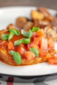 Portrait image of a slow cooker pork chop served on a white plate in a tomato sauce with tomato concasse and basil served with fried potatoes