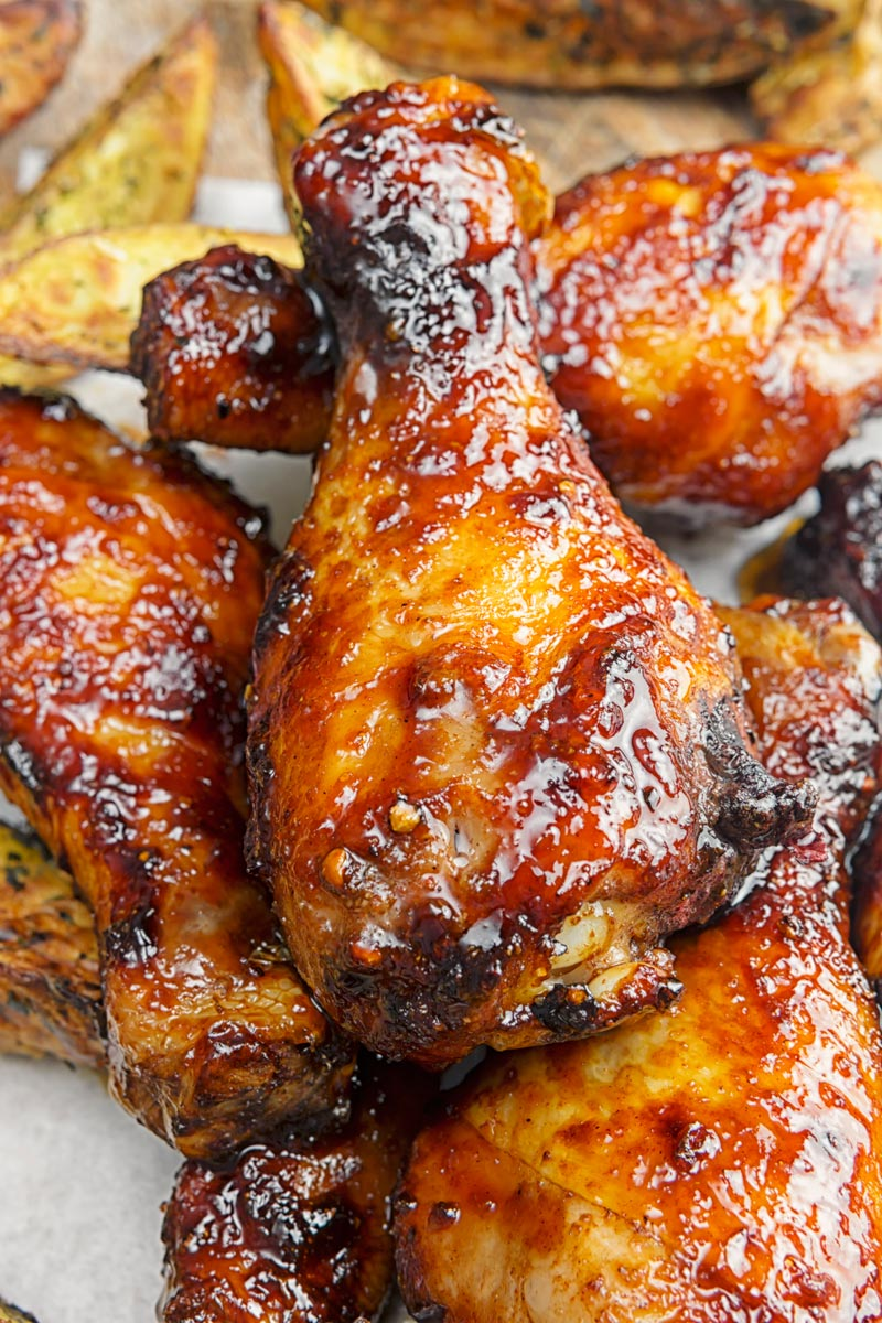 Portrait close up image of sticky glazed chicken drumsticks