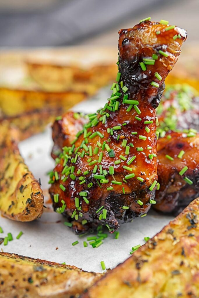 Portrait image of sticky glazed chicken drumsticks with snipped chives served with herbed potato wedges