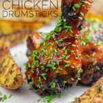 Portrait image of sticky glazed chicken drumsticks with snipped chives served with herbed potato wedges with text overlay