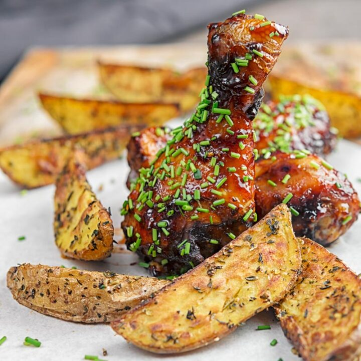 Square image of sticky glazed chicken drumsticks with snipped chives served with herbed potato wedges