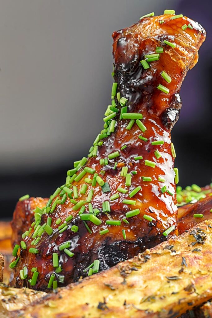 Portrait close up image of sticky glazed chicken drumsticks with snipped chives served with herbed potato wedges