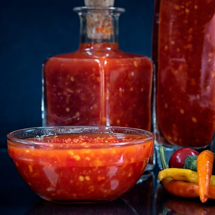 Square image of sweet chili sauce served in a dippiing bowl with chillies and bottles of sauce