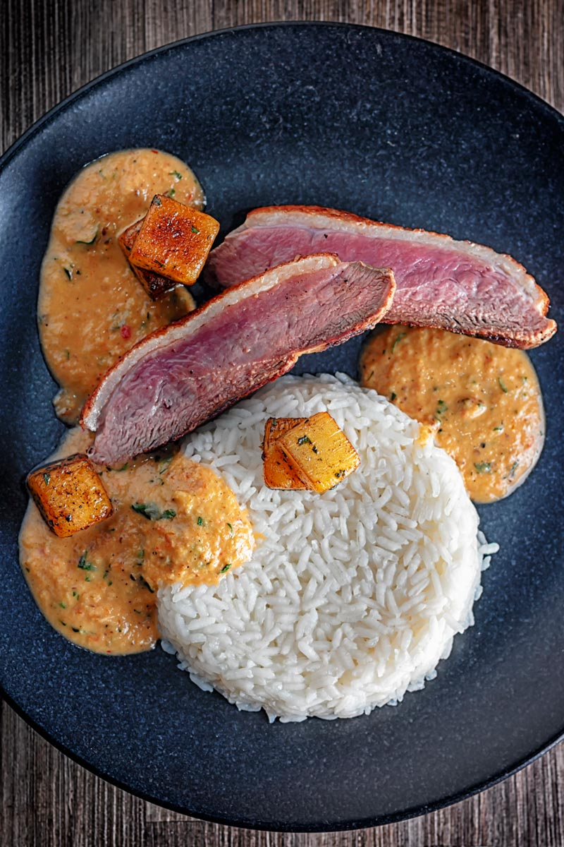 Portrait overhead image of a deconstructed Thai Duck Curry with seared pineapple and jasmine rice served on a black textured plate