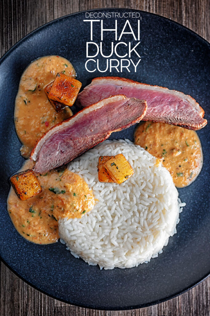 Portrait overhead image of a deconstructed Thai Duck Curry with seared pineapple and jasmine rice served on a black textured plate with text overlay