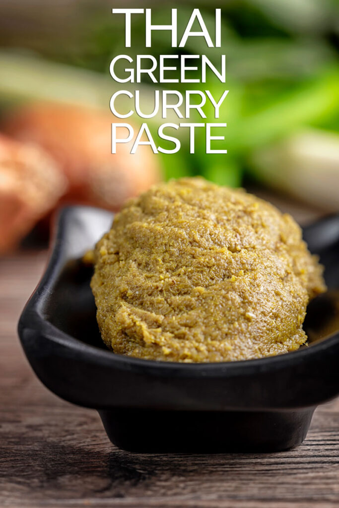 Portrait image of a homemade Thai green curry paste with ingredients for the paste in the background with text overlay