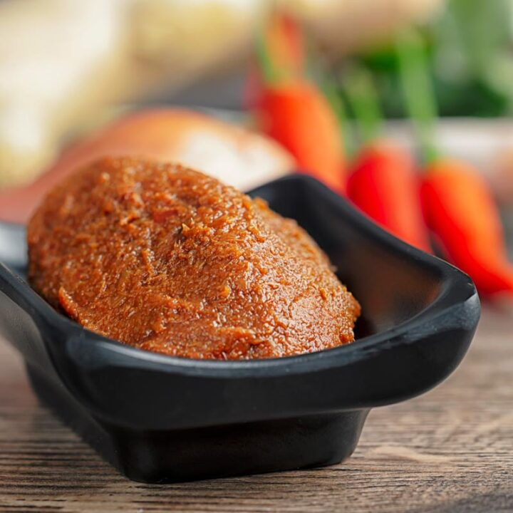 Square image of Thai red curry paste on a black serving dish with out of focus ingredients