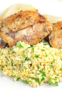 Portrait image of toasted millet served on a white plate with chicken thighs
