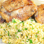 Portrait image of toasted millet served on a white plate with chicken thighs with text