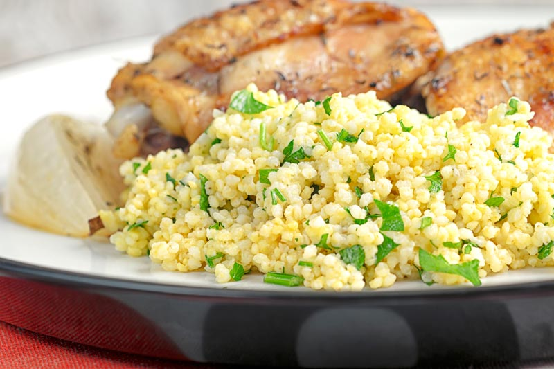 Landscape image of toasted millet served on a white plate with chicken thighs