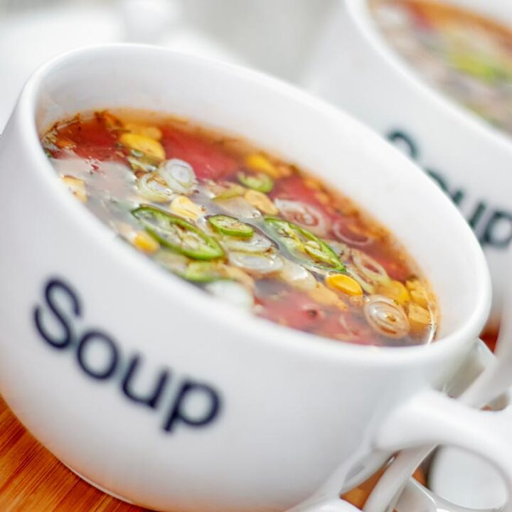 Square image of a tomato and sweetcorn broth based soup served in a white porcelain cup with soup printed on the front