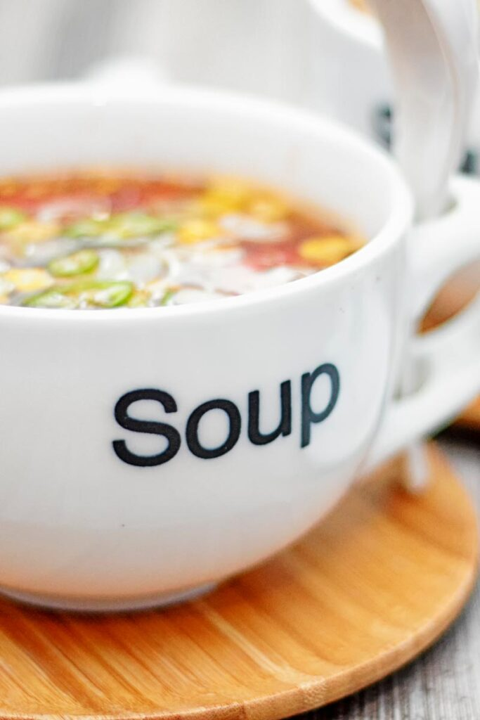 Portrait close up image of a tomato and sweetcorn broth based soup served in a white porcelain cup with soup printed on the front