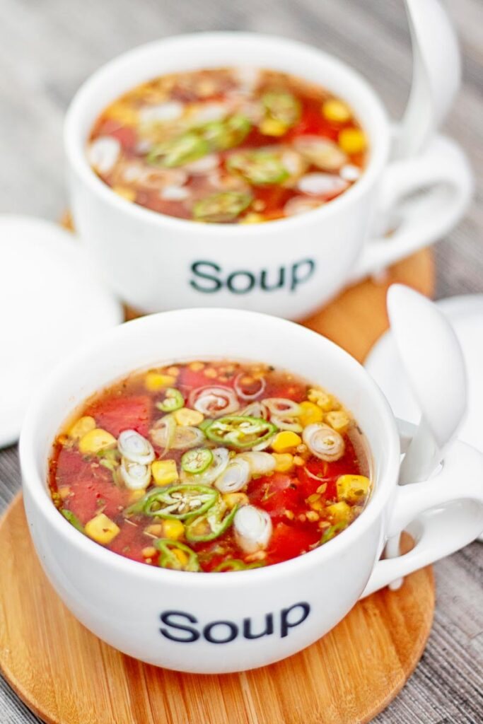 Portrait image of a tomato and sweetcorn broth based soup served in two white porcelain cups with soup printed on the front