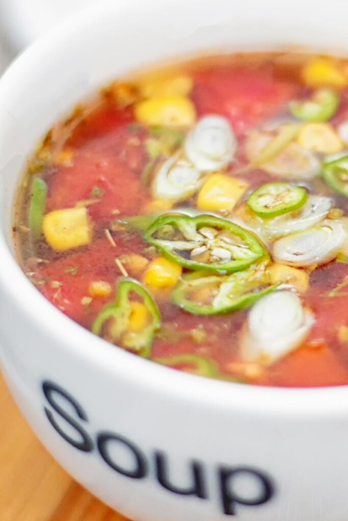 Portrait close up image of a tomato and sweetcorn broth based soup