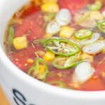 Portrait close up image of a tomato and sweetcorn broth based soup with text overlay