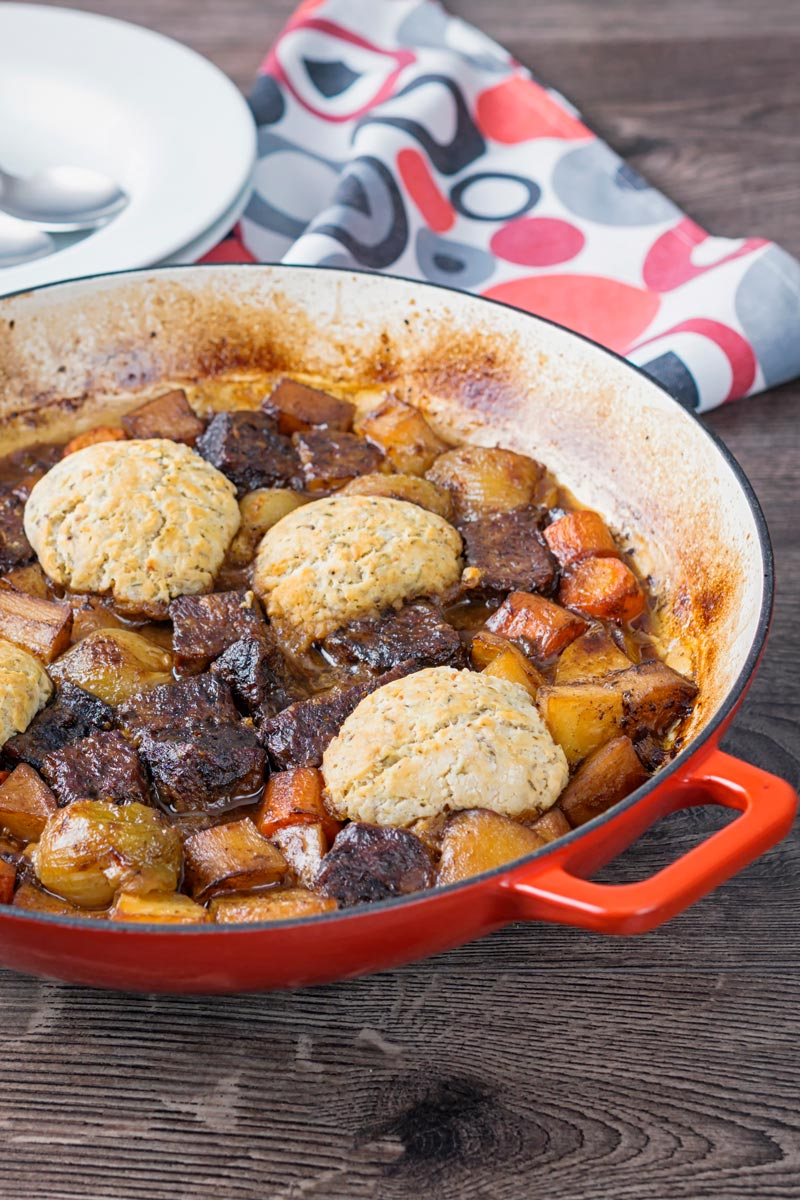 Portrait image of a beef stew with suet dumplings and lots of root vegetables cooked in a shallow cast iron pot