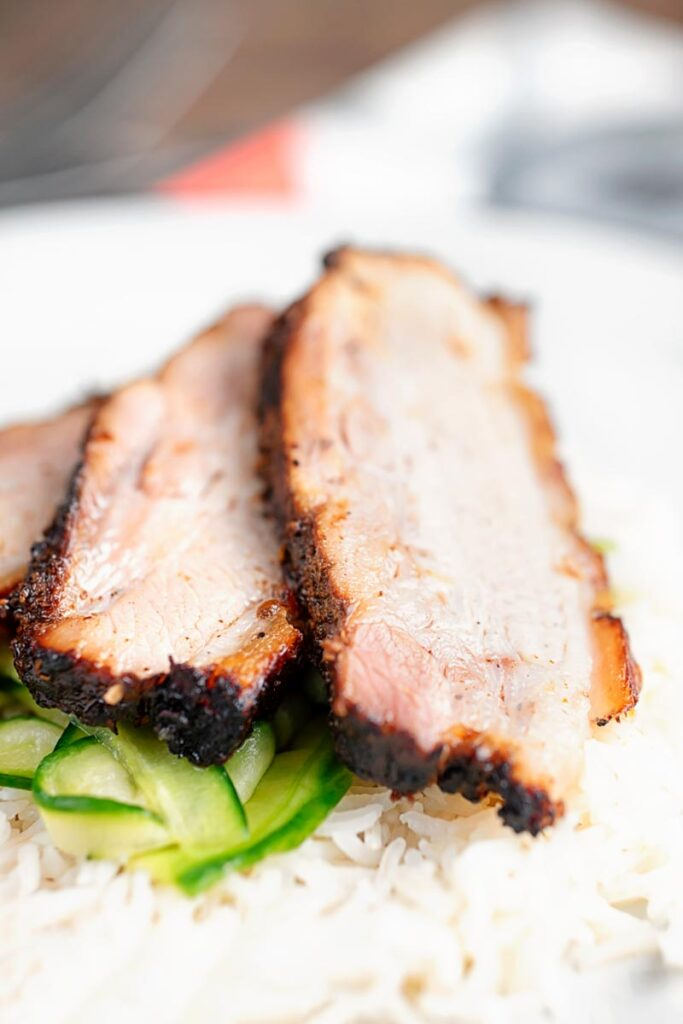 Portrait close up image of sliced crispy roast Chinese pork belly served with rice and pickled cucumbers served on a white plate