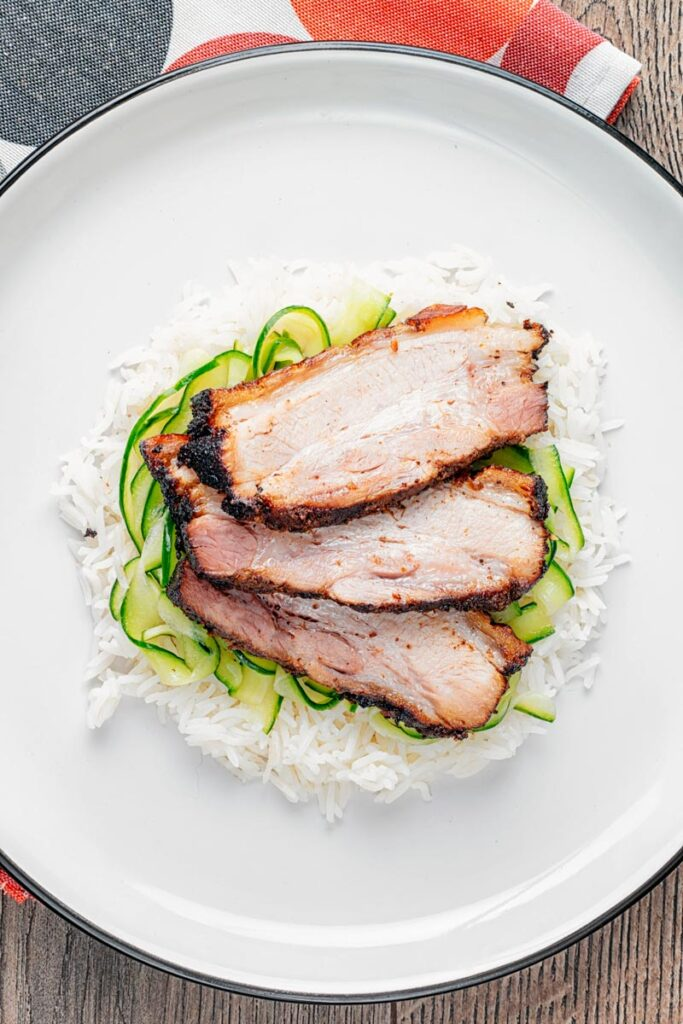 Portrait overhead image of sliced Chinese pork belly served with rice and pickled cucumbers served on a white plate