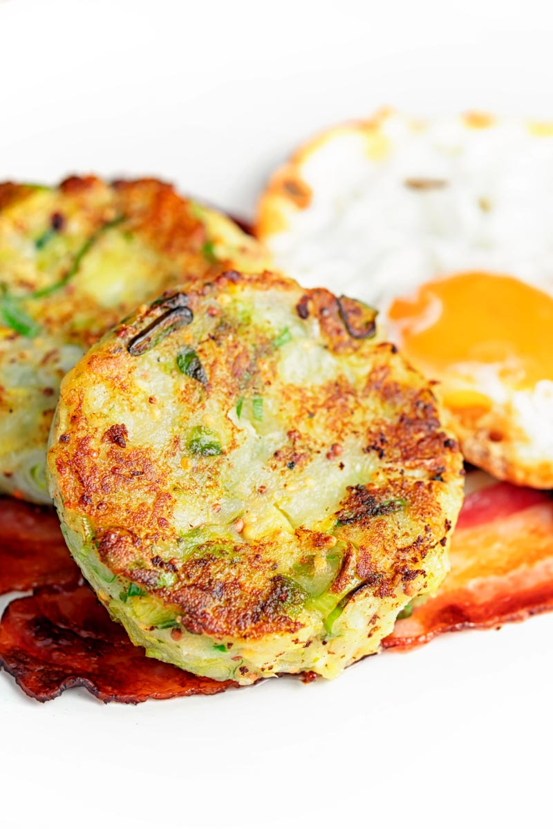 Portrait image of traditional British bubble and squeak potato cakes served with fried egg and bacon