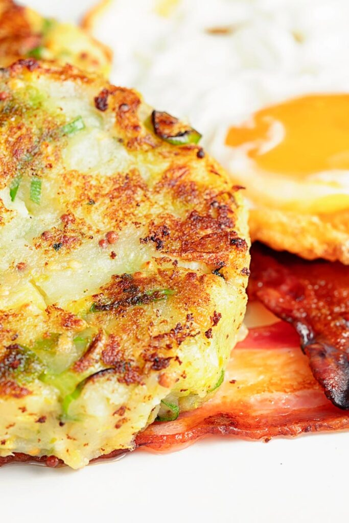 Portrait close up image of traditional British bubble and squeak potato cakes served with fried egg and bacon