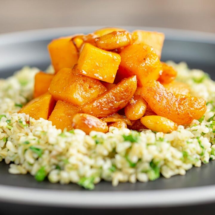 Square image of a butternut squash tagine with dried apricots and almonds served on a bed of herbed bulgur wheat