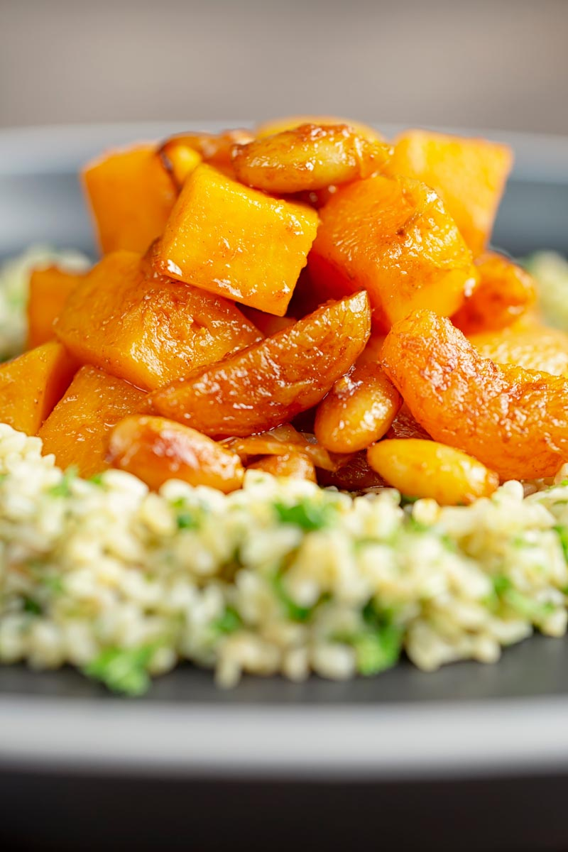 Portrait close up image of a butternut squash tagine with dried apricots and almonds served on a bed of herbed bulgur wheat