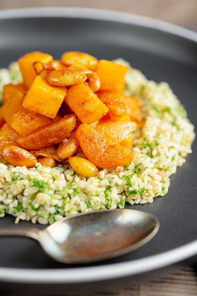 Portrait image of a butternut squash tagine with dried apricots and almonds served on a bed of herbed bulgur wheat on a black plate
