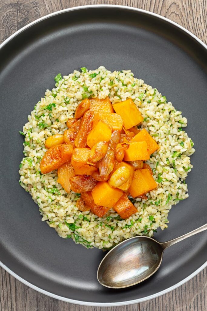 Portrait overhead image of a butternut squash tagine with dried apricots and almonds served on a bed of herbed bulgur wheat on a black plate