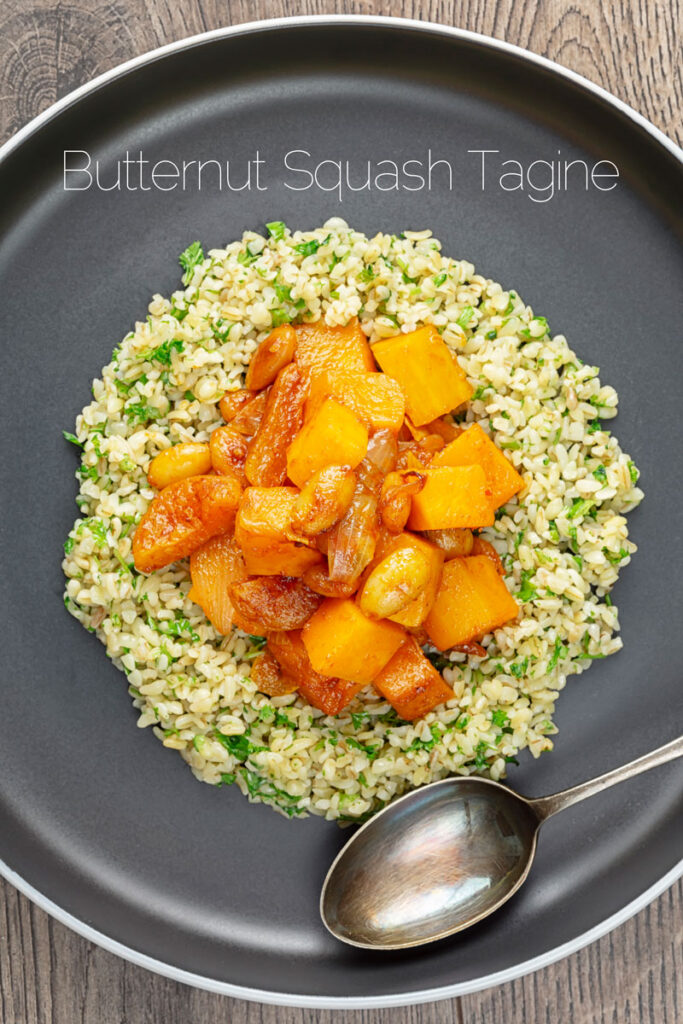 Portrait overhead image of a butternut squash tagine with dried apricots and almonds served on a bed of herbed bulgur wheat on a black plate with text overlay
