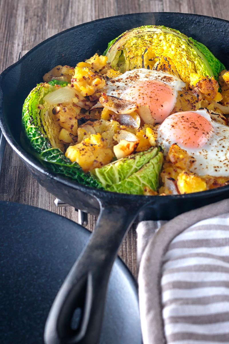Portrait image of a cabbage and potato bake with eggs cooked and served in a cast iron skillet