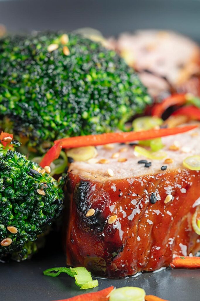 Portrait close up image of Chinese Char Siu pork tenderloin sliced and served on a dark plate with chilli spring onion and stir fried broccoli