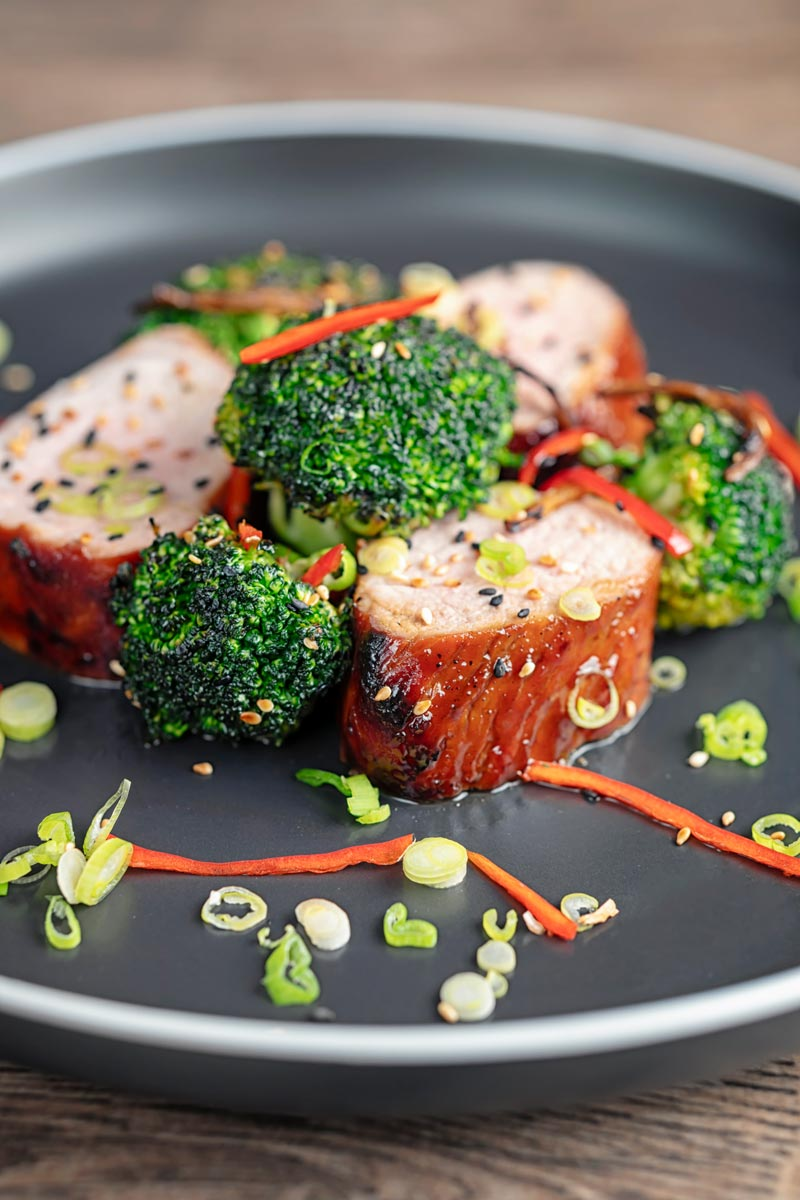 Portrait image of Chinese Char Siu pork tenderloin sliced and served on a dark plate with chilli spring onion and stir fried broccoli