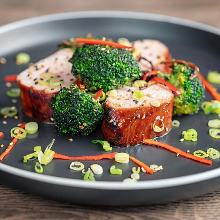 Square image of Chinese Char Siu pork tenderloin sliced and served on a dark plate with chilli spring onion and stir fried broccoli