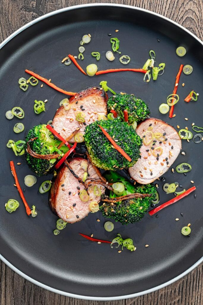 Portrait overhead image of Chinese Char Siu pork tenderloin sliced and served on a dark plate with chilli spring onion and stir fried broccoli