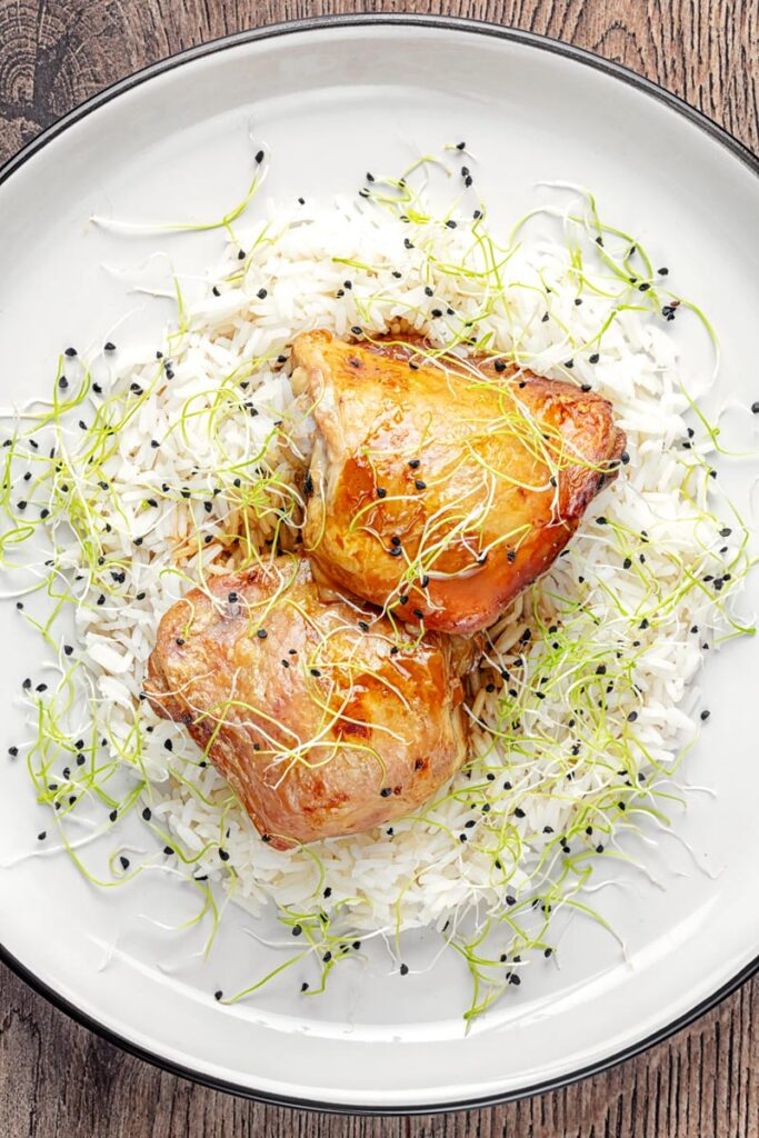 Portrait overhead image of chicken adobo made with chicken thighs served on jasmine rice served with sprouted onion seeds