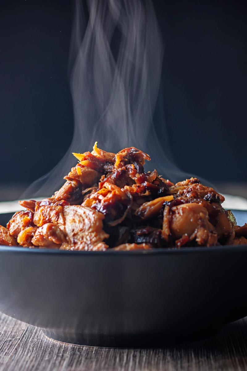 Portrait close up image of a steaming black bowl of chicken pickle or achari chicken.