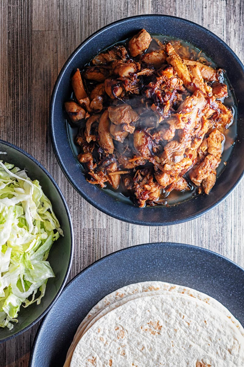 Portrait overhead image of a steaming black bowl of chicken pickle or achari chicken, flour tortilla and shredded lettuce
